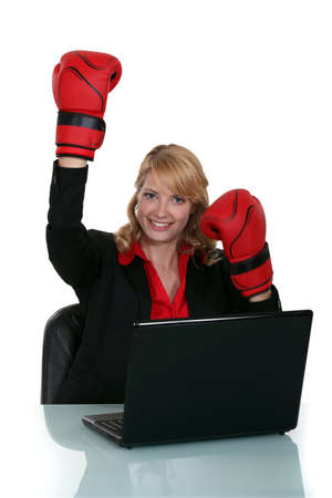Woman wearing boxing gloves whilst sat at desk photo