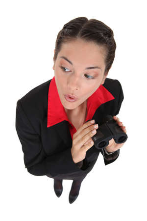 inquisitively: Curious businesswoman holding binoculars Stock Photo