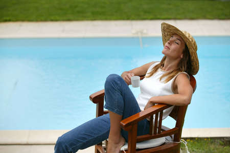 lounger: Woman sat poolside in straw hat