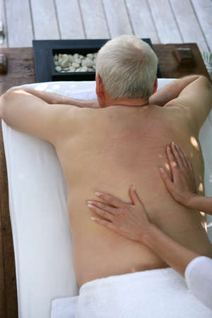 Senior man receiving a back massage photo