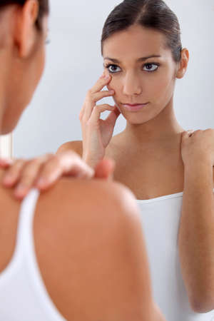 Woman looking in a mirror Stock Photo - 13582883