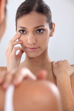 blotchy: Woman putting in her contact lenses Stock Photo