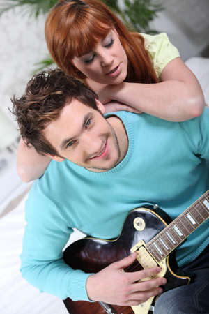 Man impressing girl by playing the guitar photo