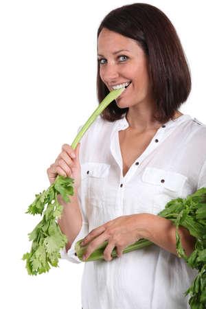 biting: Woman crunching into celery Stock Photo
