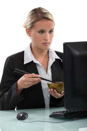 lunchbreak: Employee eating in front of her computer Stock Photo
