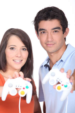 Couple stood holding video game control pads photo