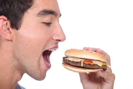 burger bun: man eating hamburger Stock Photo