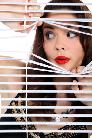 look through window: Woman spying through the blinds