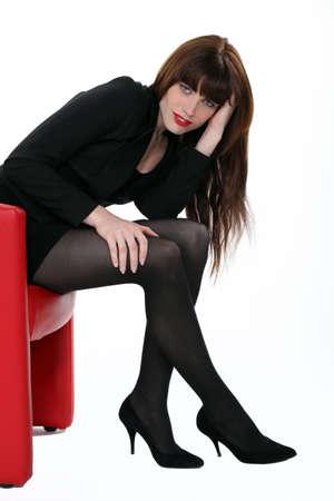 f�minit�: Femme assise dans un fauteuil rouge