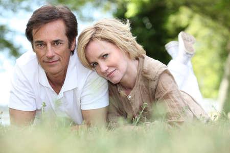 vejez feliz: Una pareja de enamorados tumbado en la hierba
