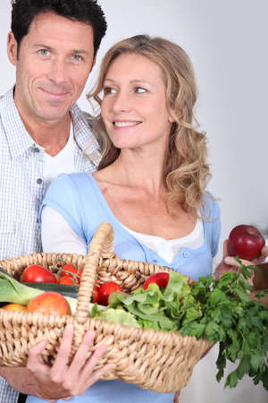 man 40 50: Wife looking at husband with vegetable basket