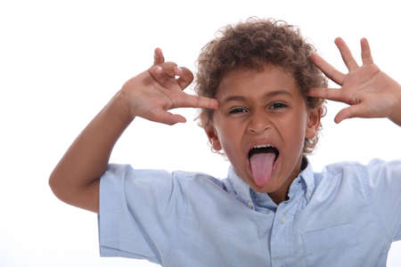 sticking: Young boy pulling a face and sticking his tongue out Stock Photo