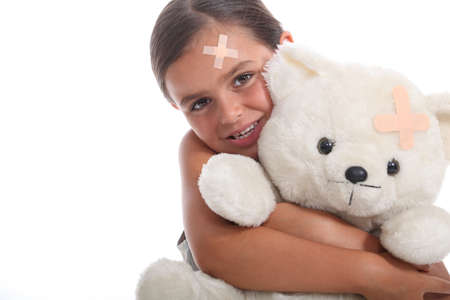 Young girl and her teddy bear, both wearing matching plasters on their foreheads Stock Photo - 13583747