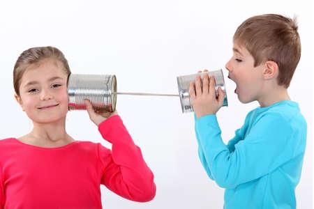 Kinderen communiceren met blikjes Stockfoto