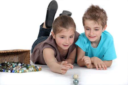 canicas: hermano y hermana jugando a las canicas juntos