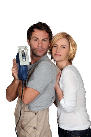 brandishing: Couple brandishing an electric jigsaw Stock Photo