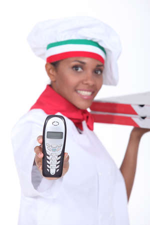 female pizza cook showing a phone photo