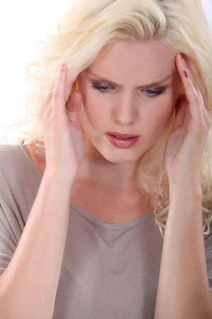 Blond woman suffering from head ache photo