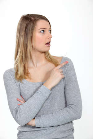 Astonished woman looking and pointing her finger sideways photo