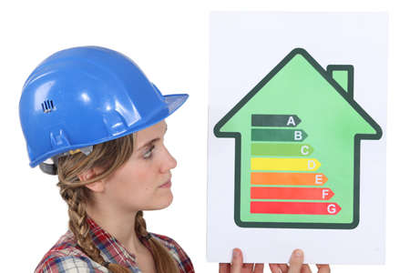 low cost: Female housebuilder with an energy rating sign Stock Photo