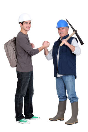 high spirited: apprentice and senior bricklayer isolated on white Stock Photo