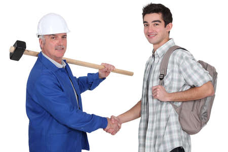 senior craftsman and apprentice shaking hands photo