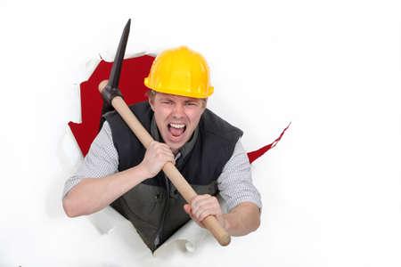 exclaiming: Tradesman bursting through a barrier Stock Photo