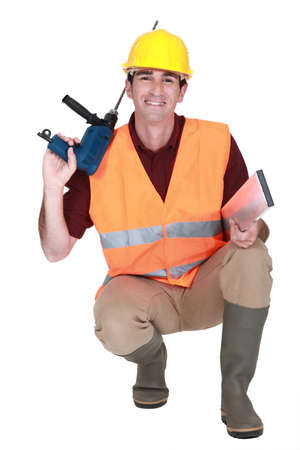 Worker kneeling with drill photo