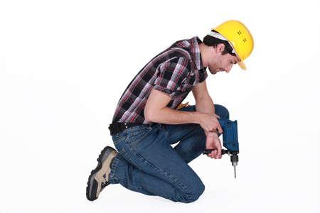 arrodillarse: Comerciante utilizando una herramienta el�ctrica