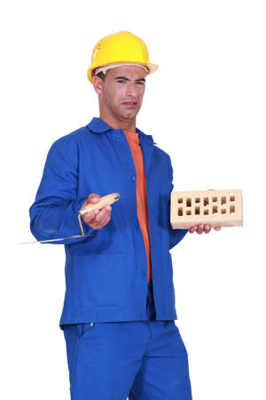 Confused mason holding brick and trowel Stock Photo - 13583267