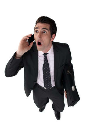 Surprised businessman with telephone and briefcase photo