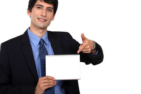 dishy: handsome young businessman pointing at spiral notebook Stock Photo
