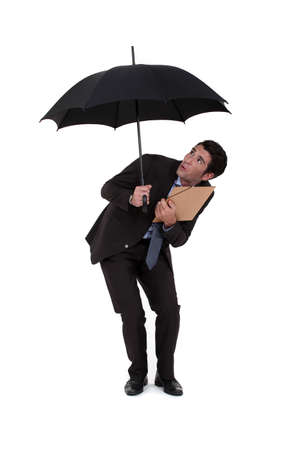 crouched: Businessman discovering a hole in his umbrella Stock Photo