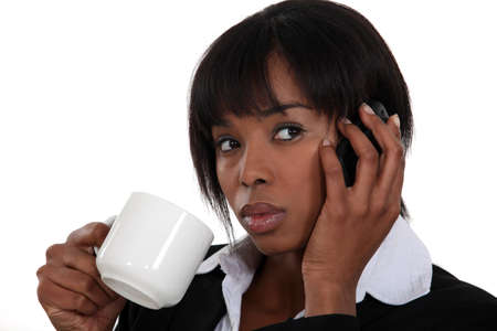 Woman drinking a cup of tea while talking on the phone Stock Photo - 13583300