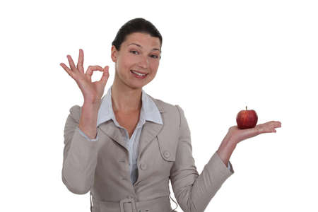 non verbal: Woman holding an apple and giving the OK sign