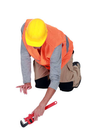 kneel down: Tradesperson using a pipe wrench Stock Photo