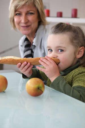 Little girl eating bread Stock Photo - 13582217