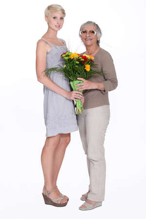 Woman giving her grandmother flowers photo