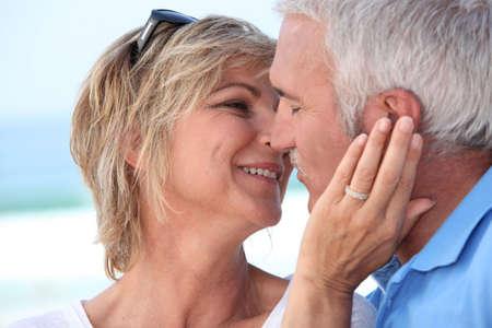 pareja besandose: Pareja de mediana edad besándose en la playa Foto de archivo