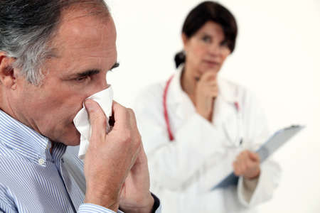 Man blowing his nose next to a doctor photo