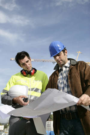 Construction workers looking at a blueprint Stock Photo - 13583357
