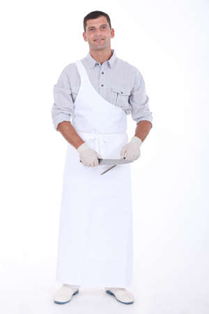 storekeeper: a butcher sharpening a knife Stock Photo