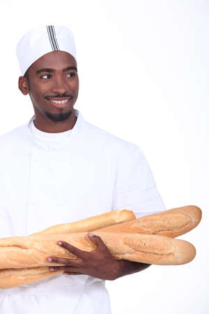 armful: Baker with an armful of baguettes