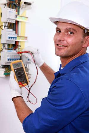 electricista: Electricista sonriente con un medidor en el medidor de electricidad
