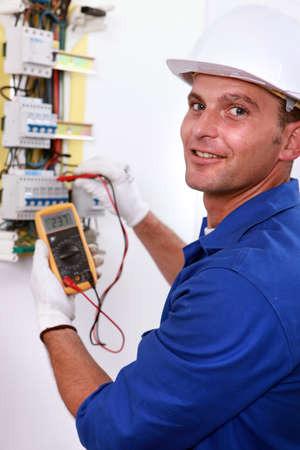 Smiling electrician using multimeter on electric meter photo