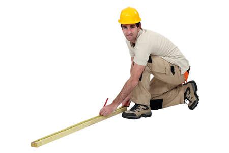 kneel: Workman taking measurements