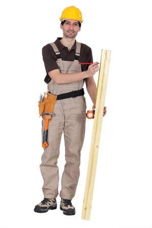 work area: Man measuring wood