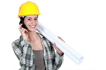 Female builder with plans and mobile telephone photo