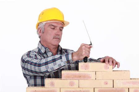 A mature mason building a wall  photo