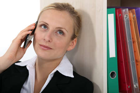 Businesswoman leaning against bookcase during call photo